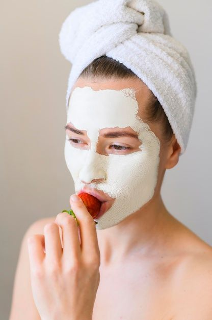 front-view-woman-with-face-mask-eating-strawberry_23-2148520258